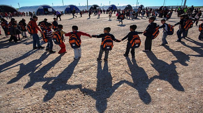 03. Syrian refugee children hold hands and form a ring while playing a game between classes in Adiyaman, which is one of 17 camps in Turkey.